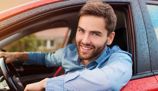 Man sat in drivers seat with head out the window smiling.