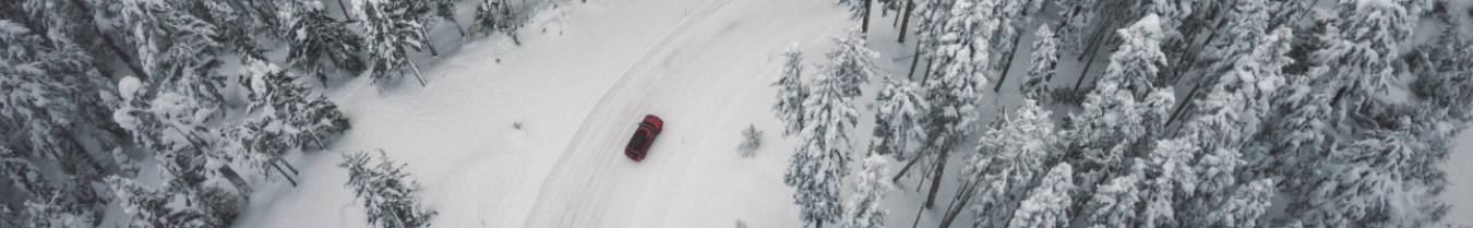 Red Car driving in the snow
