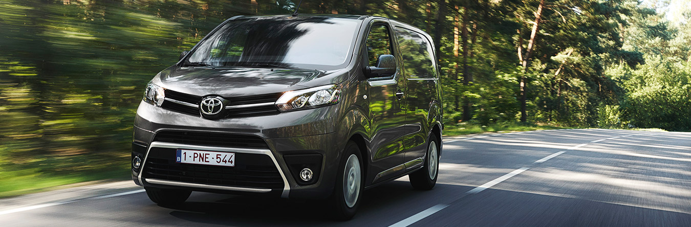 Toyota PROACE panel van in Falcon Grey driving on road.