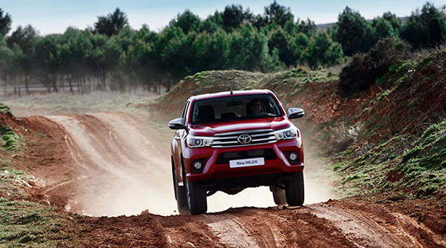Red Toyota driving off-road.