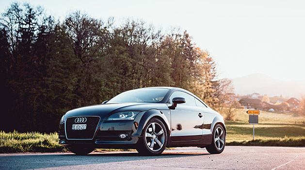 Black Audi TT parked on the road.