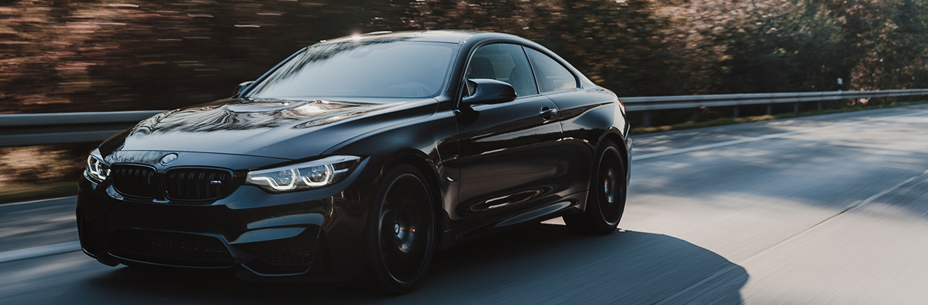 Black BMW driving on the road.