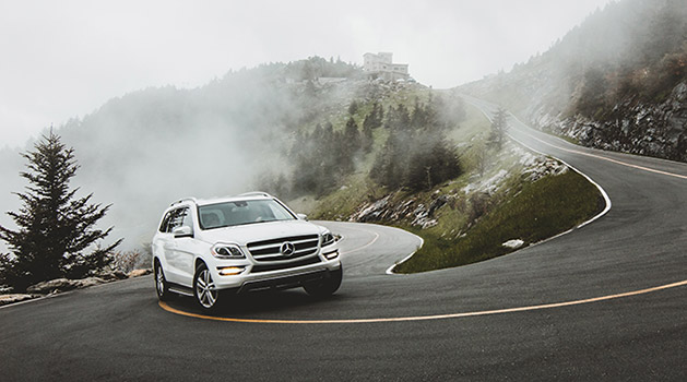 Silver Mercedes-Benz driving on the road.